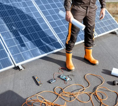 Installing solar panels, close-up on a working tools. wires and man in protective clothing standing on a rooftop with photovoltaic power station
